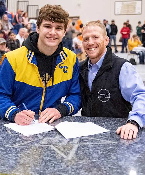 LON AUSTIN/CENTRAL OREGONIAN - Kyle Knudtson signs a letter of intent to wrestle at Eastern Oregon University while Crook County High School head coach Jake Gonzales watches. Knudtson is also planning on playing baseball at the university.