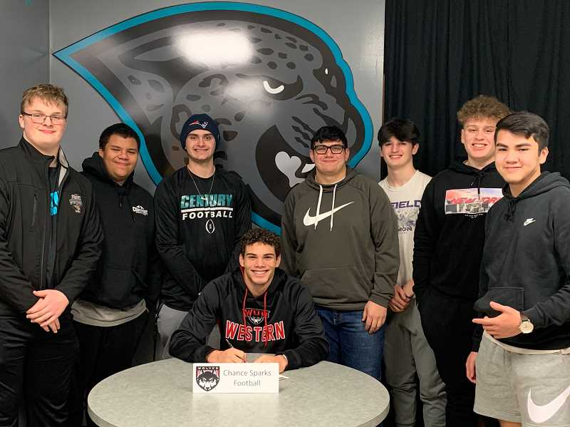 COURTESY PHOTO - Century's Chance Sparks signs his letter of intent during a ceremony Tuesday, Feb. 11, at Century High School. Sparks is surrounded by Jaguar teammates (left to right) Brody Reese, TunTun Freeman, Zander Breault, Nathaniel Miranda, Tyler Mahlman, Daunte Powell and Chris Phan.