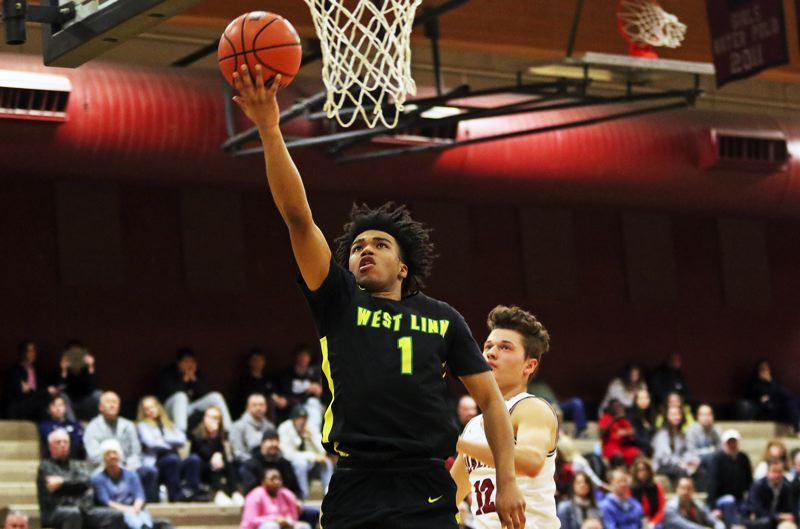 PMG PHOTO: DAN BROOD - West Linn High School senior Micah Garrett goes up to the basket for a layup during the Lions' 69-51 win at Tualatin in Friday's Three Rivers League game.