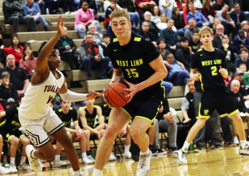 PMG PHOTO: DAN BROOD - West Linn senior post Joe Juhala (15) looks to drive to the basket during the Lions' Three Rivers League game at Tualatin. Juhala scored a game-high 22 points in the contest.