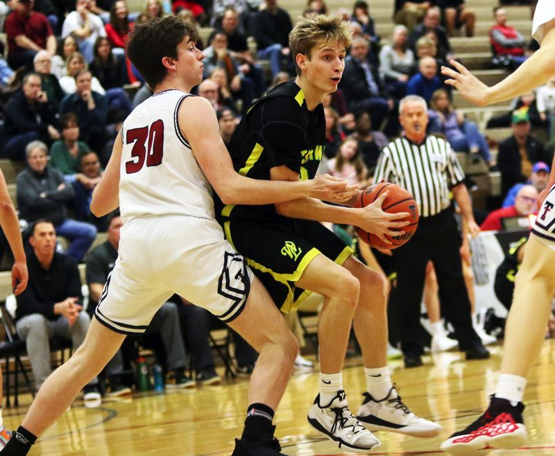PMG PHOTO: DAN BROOD - West Linn senior Colton Young (right) controls the ball against Tualatin senior Bret Robert during Friday's Three Rivers League game. The Lions got a 69-51 victory.