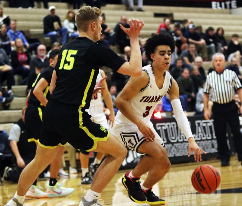PMG PHOTO: DAN BROOD - Tualatin High School sophomore Noah Ogoli (right) controls the ball on the dribble in front of West Linn senior Joe Juhala during Friday's Three Rivers League game.