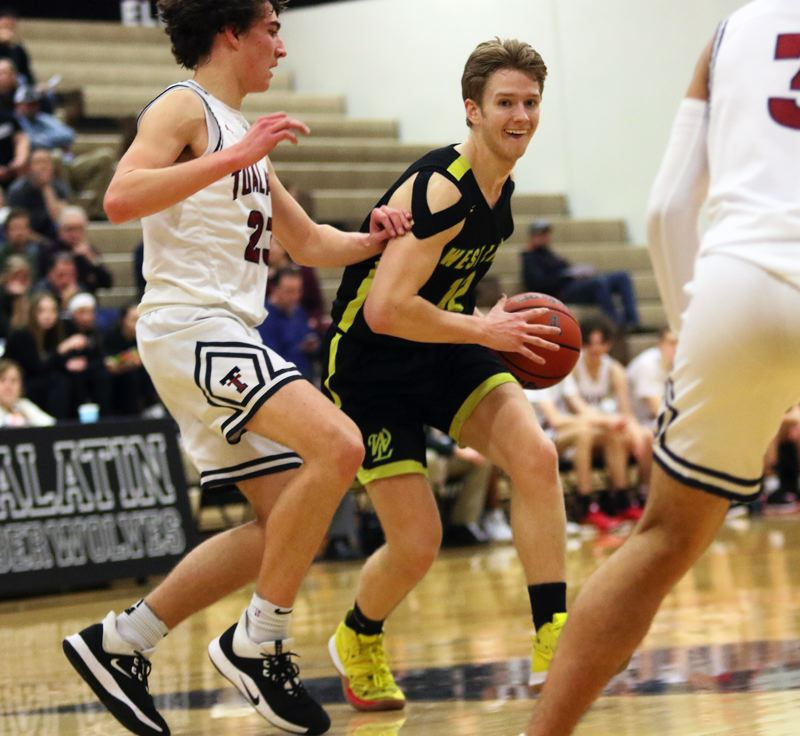 PMG PHOTO: DAN BROOD - West Linn's Parker Durbin (right) looks to work the ball inside against Tualatin sophomore Peter Burke. Durbin had 13 rebounds in the Lions' 69-51 victory.
