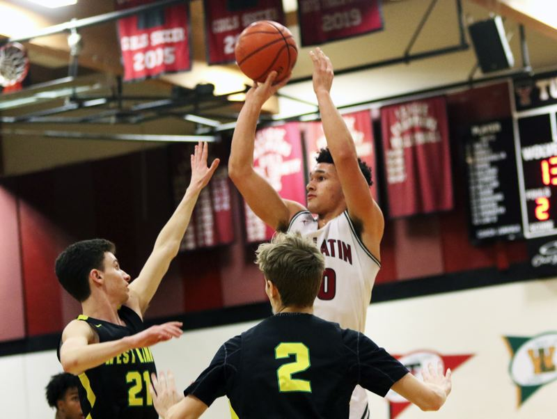 PMG PHOTO: DAN BROOD - Tualatin High School senior John Miller shoots over West Linn senior Kelton Herrick during Friday's Three Rivers League contest.