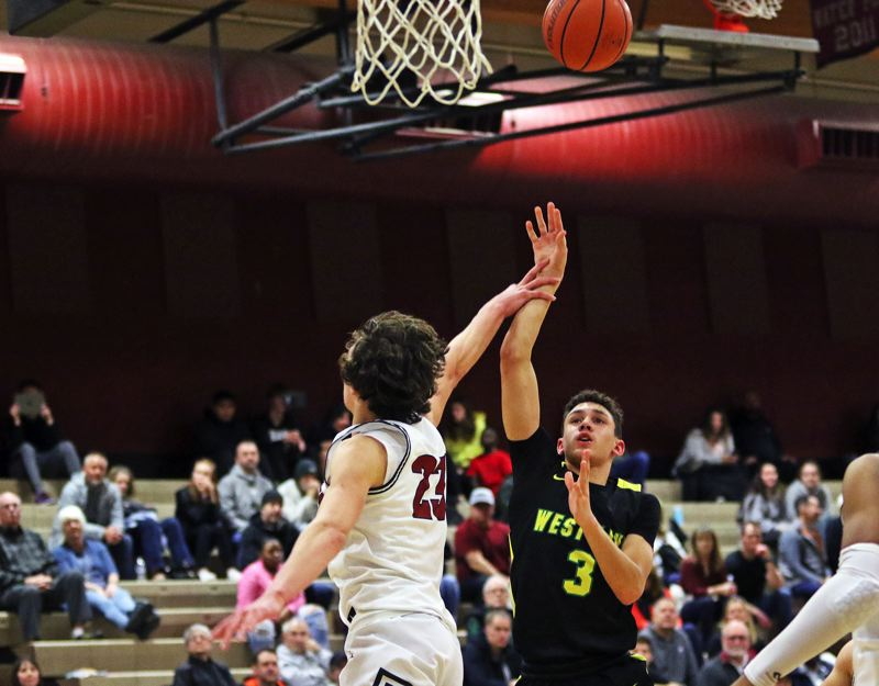 PMG PHOTO: DAN BROOD - West Linn High School freshman Jackson Shelstad (3) shoots over Tualatin sophomore Peter Burke during the Lions' 69-51 win in Friday's Three Rivers League contest.