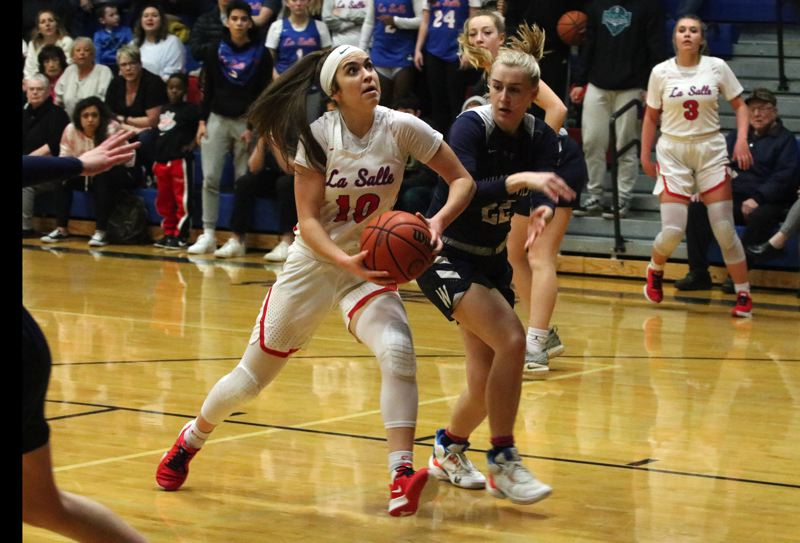 PMG PHOTO: JIM BESEDA - La Salle Prep's Amanda Sisul drives to the basket under pressure from Wilsonville's Renee Lee during the first half of Friday's Northwest Oregon Conference girls basketball game at La Salle.