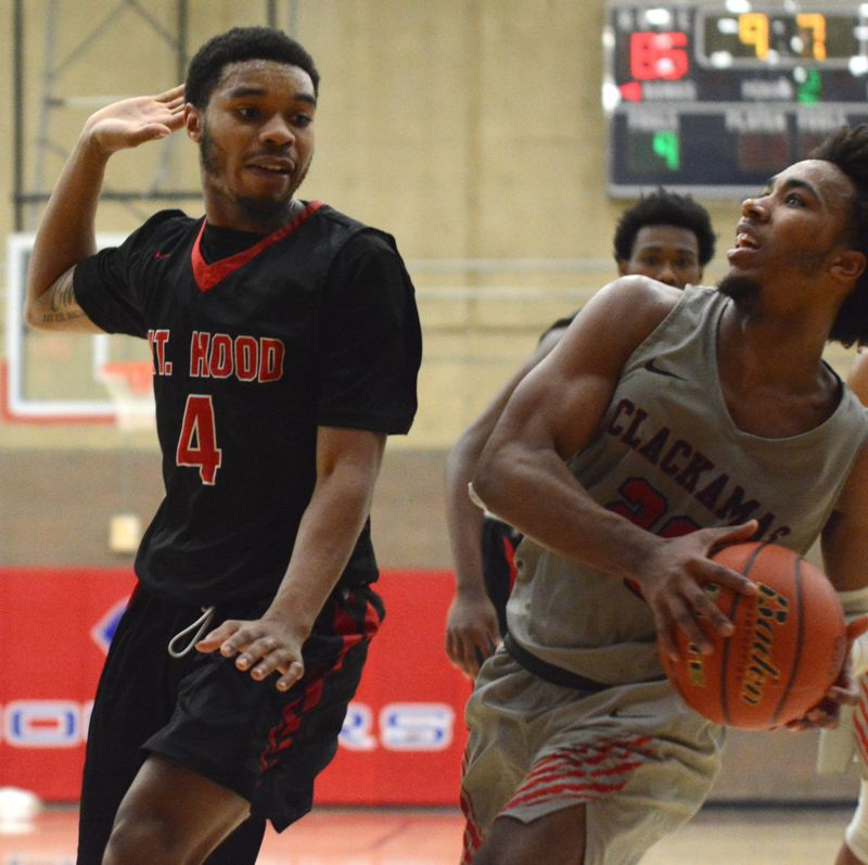 PMG PHOTO: DAVID BALL - Clackamas guard Robert Ford works to get off a shot against Mt. Hoods Davion Stringer during the Cougars 87-85 home win on Wednesday.