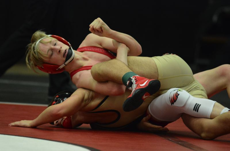 PMG PHOTO: DAVID BALL - Centennials Jeremiah Van Cleve hooks the leg of Clackamas Alejandro Wilson on his way to a pin in the 120-pound finale.