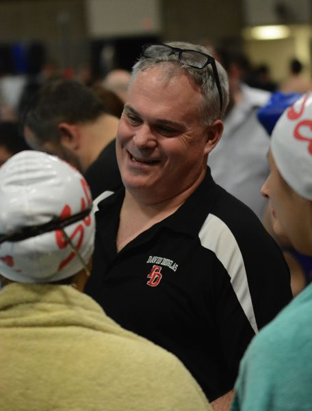 PMG PHOTO: DAVID BALL - David Douglas swim coach Jim Bowe shares a laugh with his swimmers during a break in the action. The Scots swept both the boys and girls district titles Saturday.