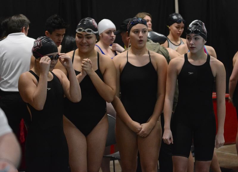 PMG PHOTO: DAVID BALL - Members of Sandys 200-yard freestyle relay wait on the pool deck for the start of their race.