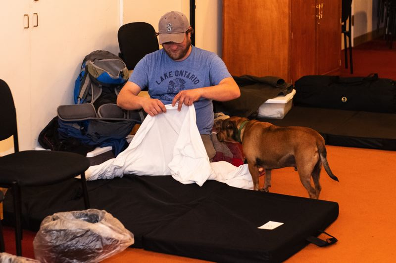 PMG PHOTO: CHRISTOPHER OERTELL - John Carlin gets a sleeping pad ready for himself and his dog, Brando, at the homeless shelter at the Forest Grove United Church of Christ in November 2018.