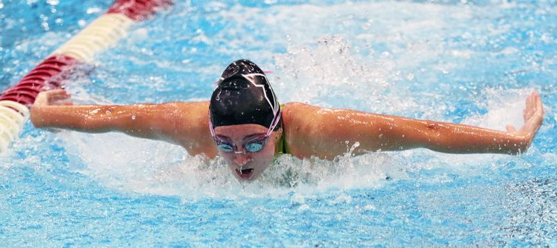 PMG PHOTO: DAN BROOD - Tigard High School sophomore Abbigale Elliott competes in the 100-yard butterfly event at the Three Rivers League district meet on Saturday.