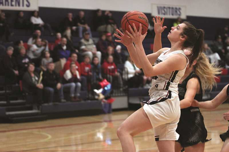 PMG PHOTO: PHIL HAWKINS - Kennedy junior Ellie Cantu goes up for a layup against the Rainier Columbians on Thursday. Cantu scored 15 points to help lead the Trojans to a 26-point victory.