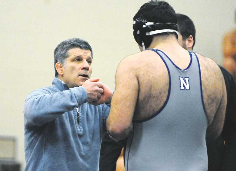 GRAPHIC PHOTO: GARY ALLEN - NHS coach Neil Russo instructs a wrestler during the district tournament at Liberty High School on Saturday.