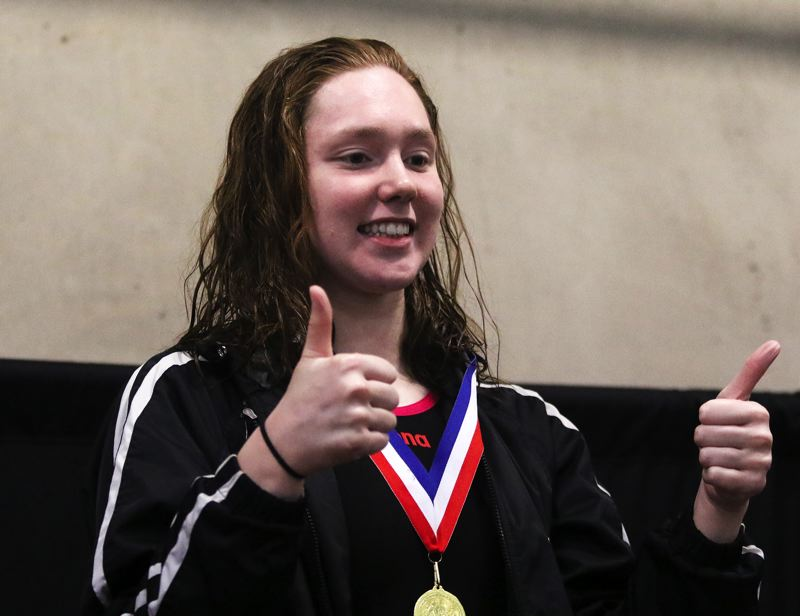 PMG PHOTO: DAN BROOD - Tualatin High School senior Abbi Karsseboom receives her championship medal after winning the 500-yard freestyle race at the Three Rivers League district swim meet for the third straight year.