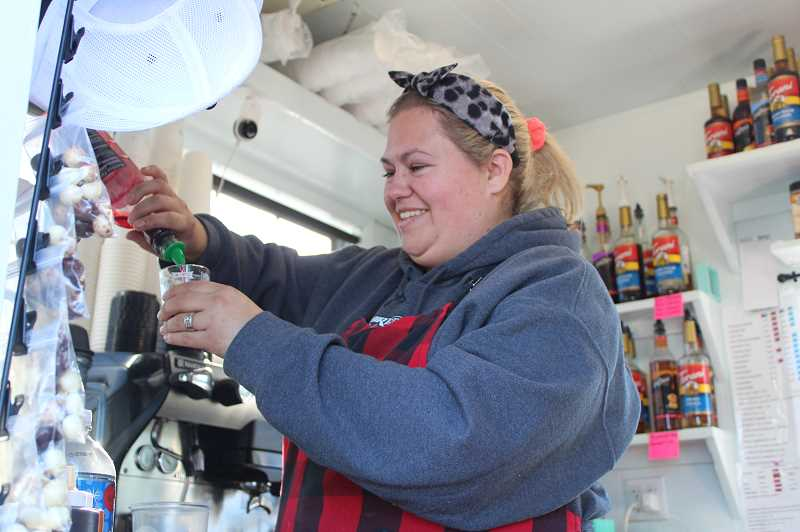 DESIREE BERGSTROM/MADRAS PIONEER - Stevie Myers, owner of Get Roasted Coffee Co., measures out several flavoring syrups to go into a house drink that some regulars order. The recipe was created by, and named after, her niece who works in the stand.