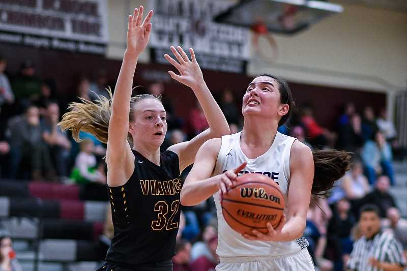 PMG PHOTO: CHRISTOPHER OERTELL - Glencoe's Jayda Lee (14) goesup for a layup with Forest Grove's Lily Everson (32) defending during a girls basketball game at Glencoe High School in Hillsboro, Ore., on Tuesday, Feb. 18, 2020.