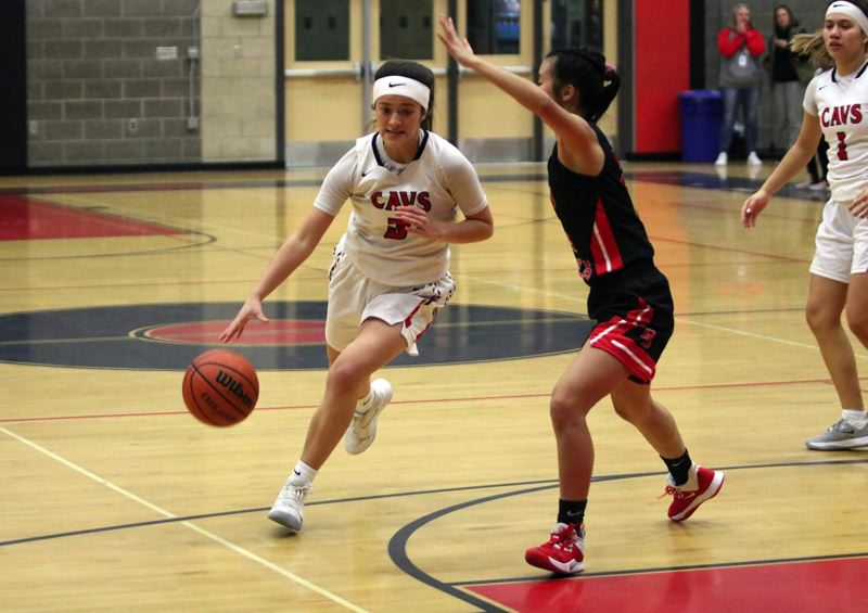 PMG PHOTO: JIM BESEDA - Clackamas guard Bella Garcia puts the ball on the floor under pressure from David Douglas' Ziling Zhen during the first half of Tuesday's Mt. Hood Conference girls basketball game at Clackamas.