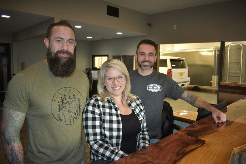 PMG PHOTO: SHANNON O. WELLS - Northwest Signs & Apparels three partners, from left, Chris Brittain, his wife Brittany Brittain, and Rob Faria now operate from an expanded location at 1090 N.E. Eighth St.