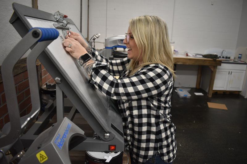 PMG PHOTO: SHANNON O. WELLS - As Northwest Signs aparrel specialist, Brittany Brittain works on a logo design in the businesss new workshop at Northeast Eighth Street and Cleveland Avenue.