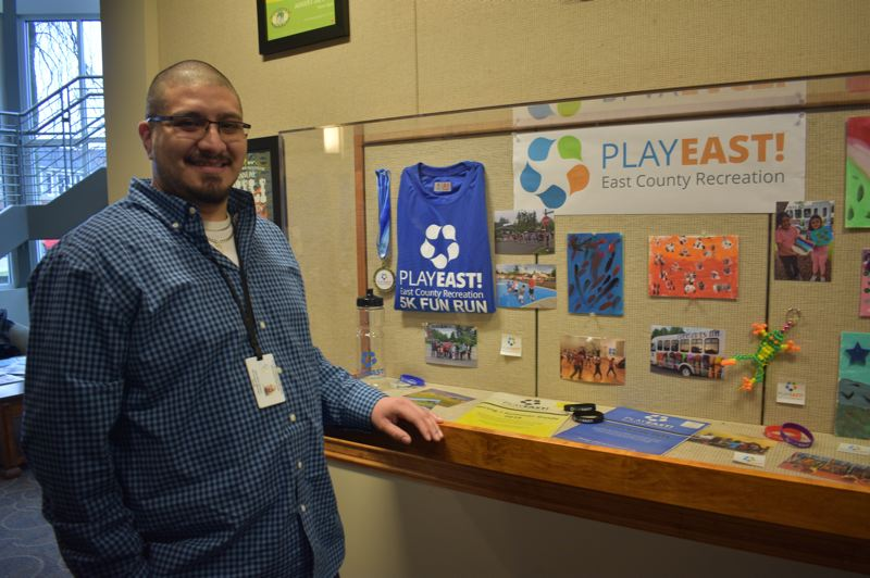 PMG PHOTO: SHANNON O. WELLS - Jairo Rios-Campos, program director for the Play East! recreation program, beams by a display case in the Fairview City Hall lobby that highlights the range of sports and activities the program offers local children and teens.
