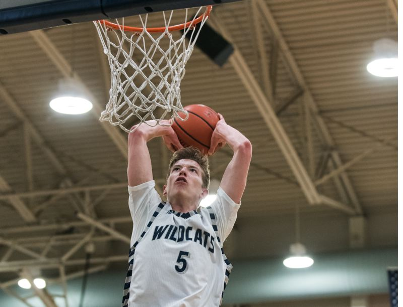 COURTESY PHOTO: GREG ARTMAN - Wilsonville junior Riley Scanlan throws down a two-handed dunk Tuesday against Scappoose.