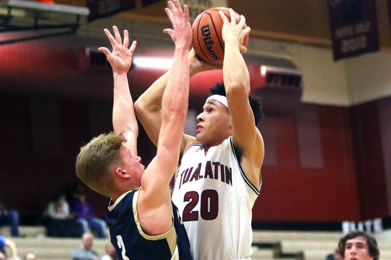 PMG PHOTO: DAN BROOD - Tualatin High School senior John Miller (20) shoots over Canby's Tyler Mead during the teams' first meeting this season. The Wolves and Cougars will have their rematch tonight at Canby High School.