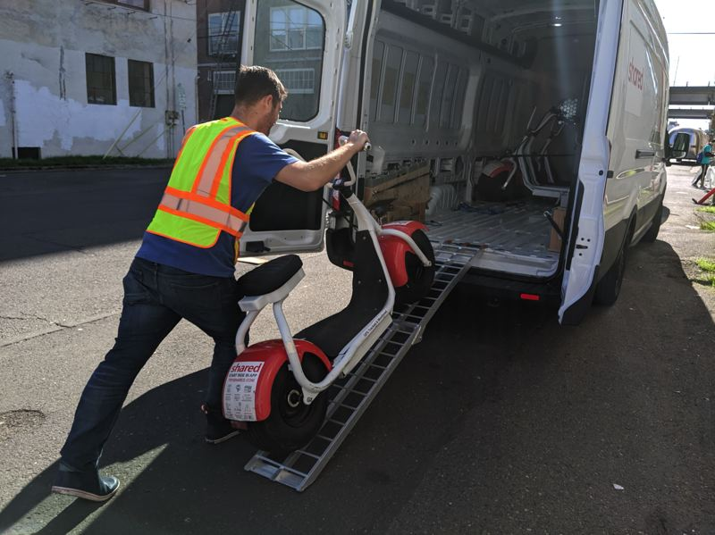 PMG: JOSEPH GALLIVAN - End of the road: Summer 2019 and Owen Christopher loads up Shared scooters for maintenance. The 200 chunky ebikes have been pulled from Portland due to lack of funding.