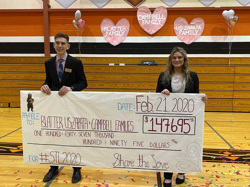 PMG PHOTO: KRISTEN WOHLERS - Share the Love coordinators Clay Sperl and Cori Oster show off the check in the amount of $147,695.45.