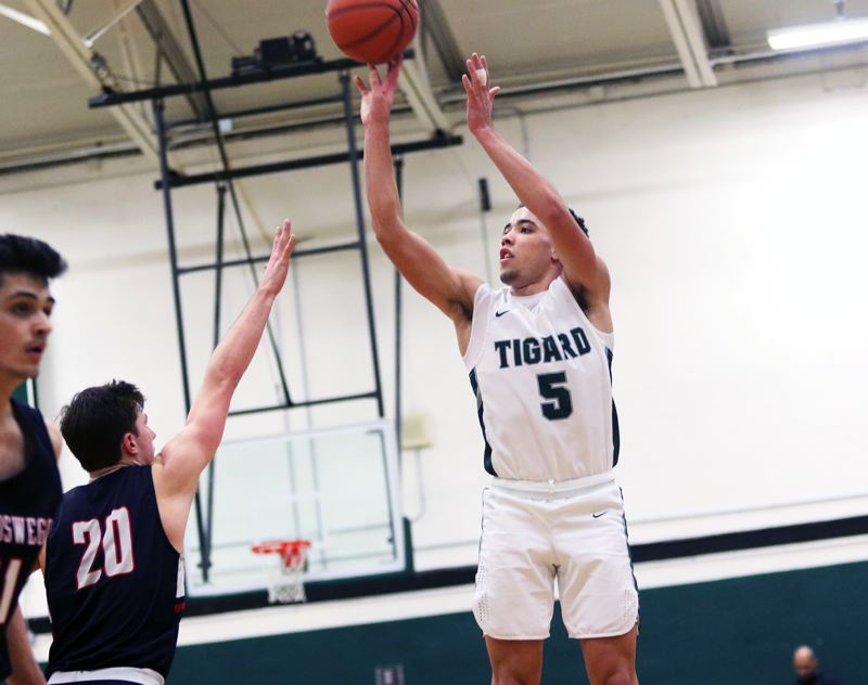 PMG PHOTO: DAN BROOD - Tigard High School junior Drew Carter (5) takes a jump shot during the Tigers' Three Rivers League game with Lake Oswego on Friday.