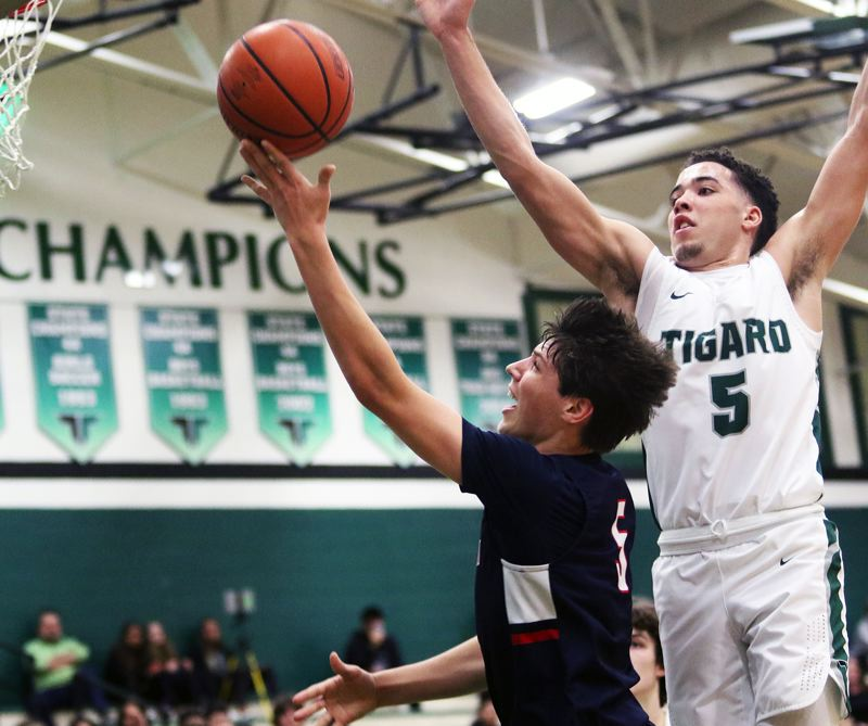 PMG PHOTO: DAN BROOD - Lake Oswego senior Casey Graver (left) tries to go up to the basket against Tigard junior Drew Carter during Friday's Three Rivers League contest.