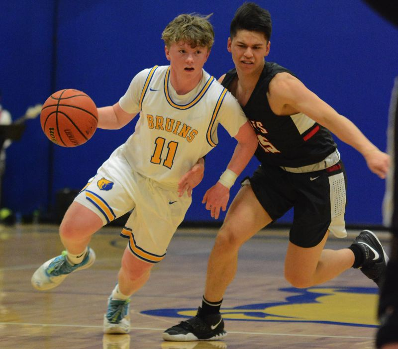PMG PHOTO: DAVID BALL - Barlows Connor Hills drives inside the arc against David Douglas defender Trenton Templeton during the Bruins 80-51 home win Friday.