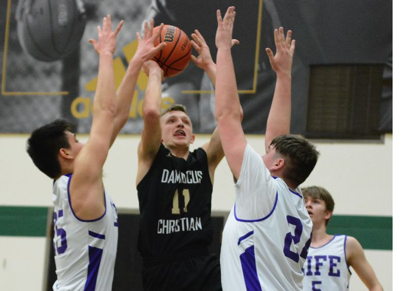 PMG PHOTO: DAVID BALL - Damascus Christians Micah Colburn fights through a crowd of defenders for a first-half bucket. He would hit the winning 3 with 5.6 seconds left.