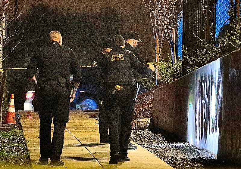 DAVID F. ASHTON - Members of the Portland Police Gun Violence Reduction Team look for bullet strikes on the retaining wall below the new Starbucks in Creston-Kenilworth.