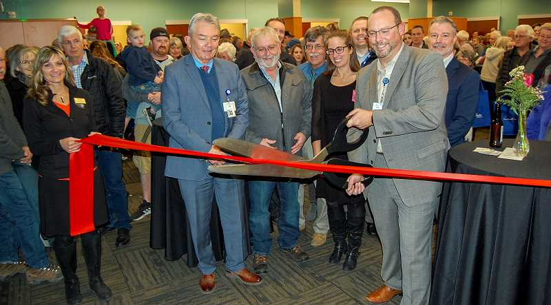 RAMONA MCCALLISTER - Becky Munn, left, holds the ribbon as Todd Shields, vice president of administration at St. Charles Prineville, cuts the ribbon for the official grand opening of the new expansion of the hospital, with St. Charles staff and visitors looking on in the background.