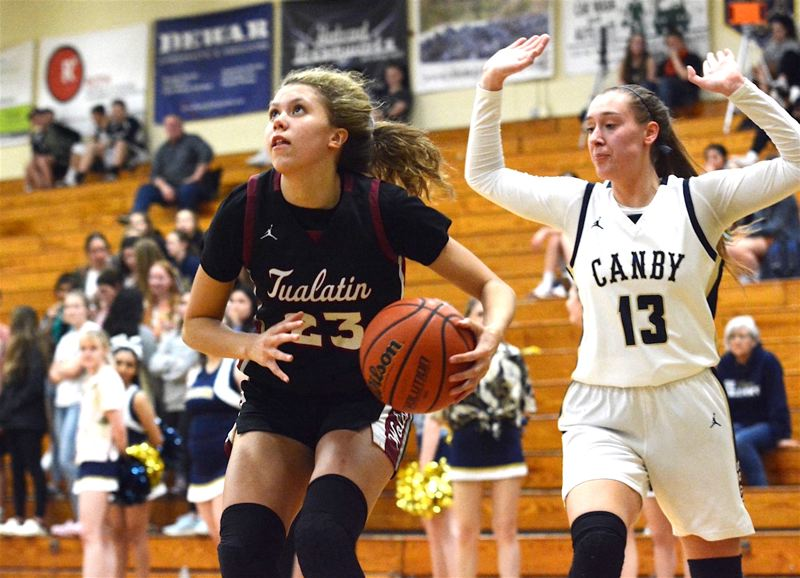 PMG PHOTO: DEREK WILEY - Tualatin High School freshman Tabi Searle (left) drives to the basket during the Timberwolves' Three Rivers League victory at Canby on Friday.