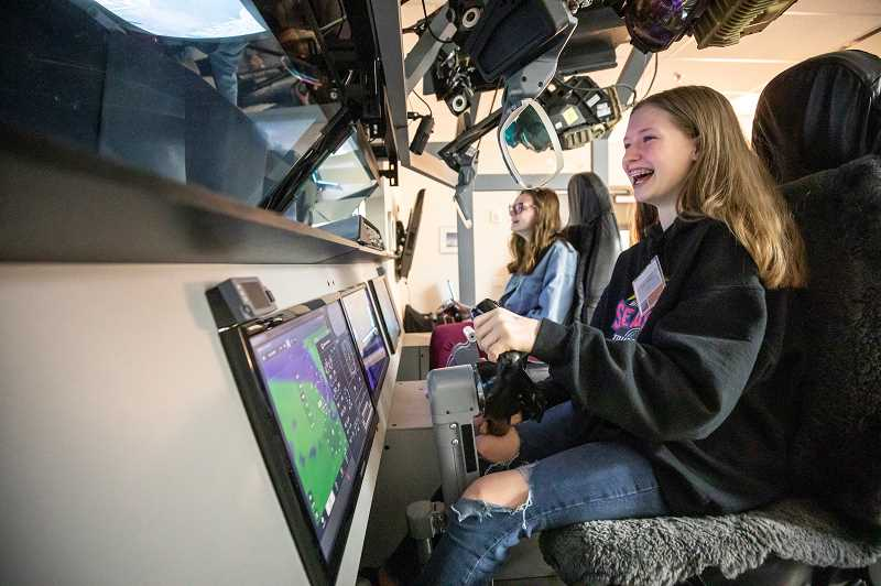 "PMG PHOTO: JONATHAN HOUSE - Grace Wilson avoids crashing her plane during a ride in the Collins Aerospace flight simulator at the 'Introduce a Girl to Engineering"" event Friday."