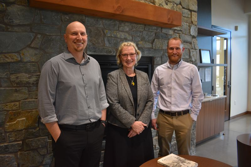 PMG PHOTO: SHANNON O. WELLS - Clackamas County Bank President Cathy Stuchlik, center, and her sons Justin, left, and Jarrett, who have leadership roles in the bank, smile by the lobby fireplace in the new Gresham bank branch on that quietly opened on Northeast Burnside Road in early January.