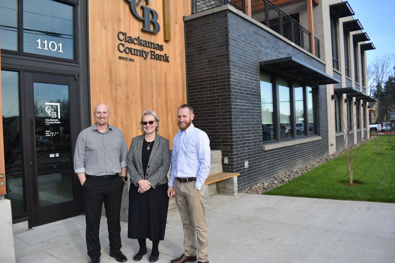 PMG PHOTO: SHANNON O. WELLS - Clackamas County Bank President Cathy Stuchlik, center, and her sons Justin, left, and Jarrett, show off the striking exterior Gresham bank branch at 1101 N.E. Burnside Road.