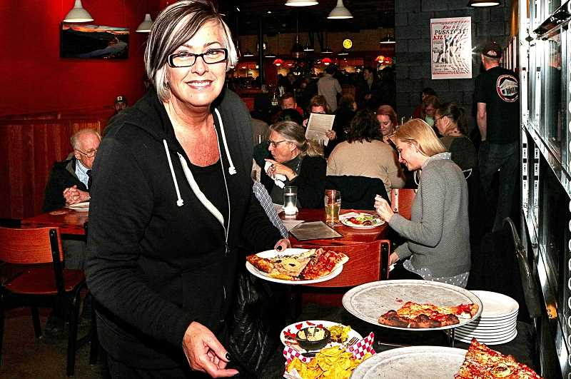DAVID F. ASHTON - Penny Gavitt of Woodstock KeyBank serves herself at the salad and pizza buffet provided by Double Mountain Brewpub at the WCBA Annual Meeting.