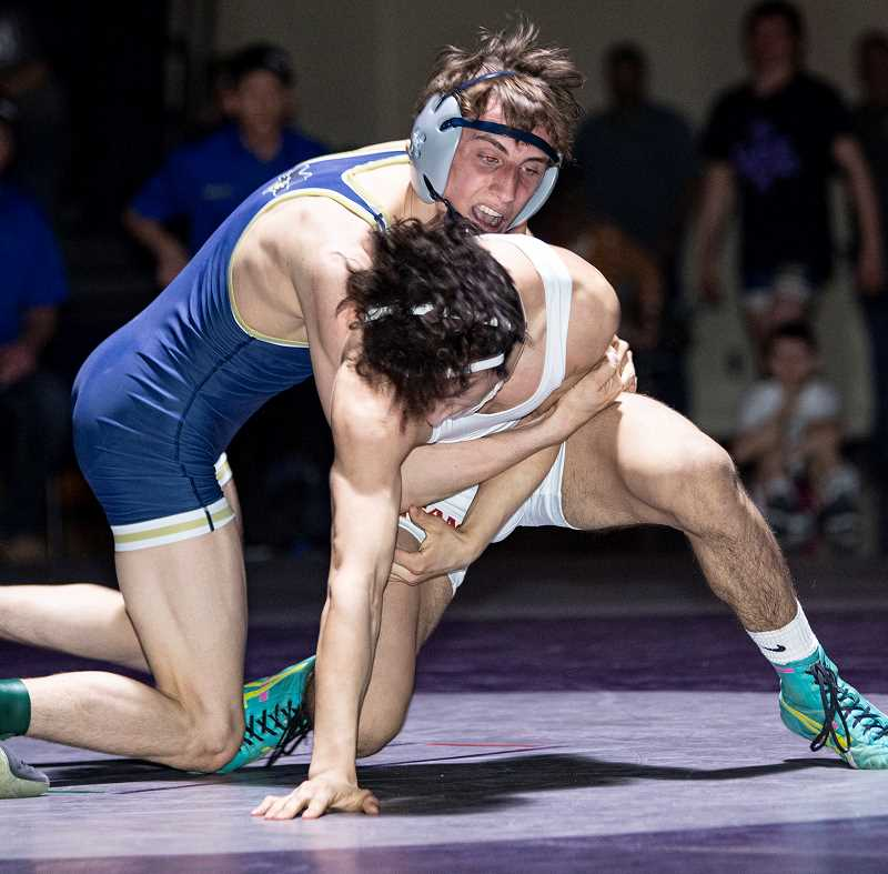 LON AUSTIN/CENTRAL OREGONIAN - Zach Mauras works to control Redmond's Junior Downing during the championship match at 132 pounds. Mauras edged Downing 8-7 to win the match as the Cowboys easily won the district championships.
