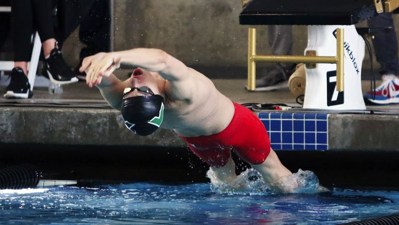 PMG PHOTO: DAN BROOD - Nathaniel Whitehead, a junior on the Tigard High School boys swim team, takes off in the 100-yard backstroke finals Saturday at the Class 6A state swimming championships.