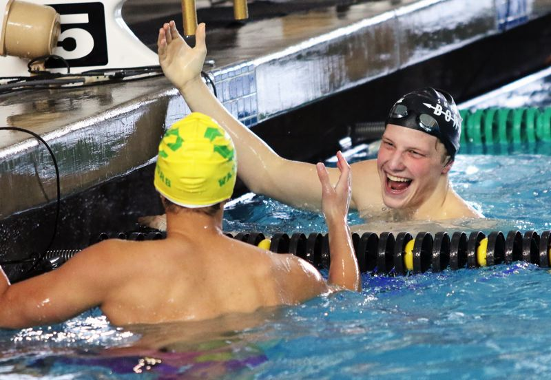 PMG PHOTO: DAN BROOD - Sherwood High School senior Jacob Folsom (right) congratulates Cleveland sophomore Cody Soo following the 100-yard freestyle event at the Class 6A state swimming championships. Soo edged Folsom by .05 seconds for the title.