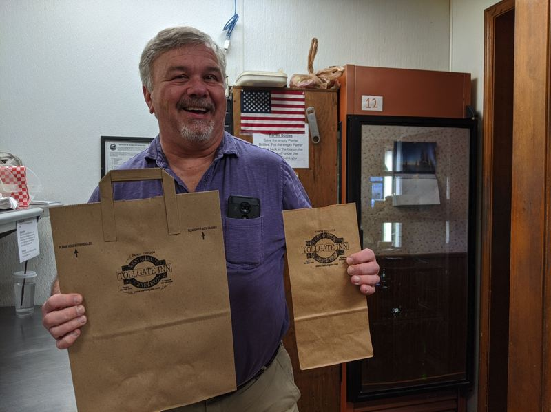 PMG PHOTO: BRITTANY ALLEN - Tollgate Inn Restaurant owner utilizes bag ban to his advantage to market himself with stamps on his paper to-go bags.
