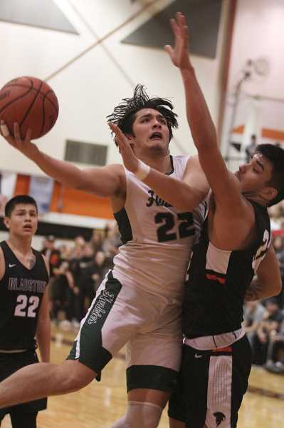 PMG PHOTO: PHIL HAWKINS - North Marion senior Sergio Jimenez absorbs contact from Gladstone junior Jeremy De Voe for a layup in the fourth quarter of the Huskies' 58-54 loss to the Gladiators.Jimenez (24 points) and De Voe (15) led their teams in scoring, respectively.