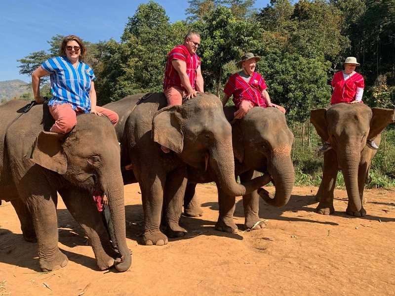 COURTESY PHOTO - Roy and Carolyne Houston, on the right, and his stepson and daughter-in-law rode elephants on a visit to Thailand. Getting onto the gentle giants was tricky.