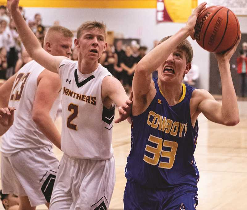 LON AUSTIN/CENTRAL OREGONIAN - Cayden Lowenbach goes up for two of his six points as the Cowboys clinched the Intermounain Conference championship with a 63-59 victory over the Redmond Panthers Tuesday night in Redmond.