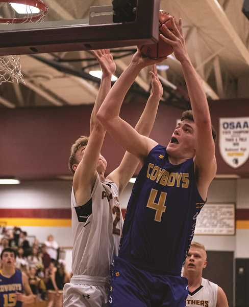 LON AUSTIN/CENTRAL OREGONIAN - Caleb Arnold goes to the basket for two of his game-high 25 points in the Cowboys 63-59 victory over the Redmond Panthers, Tuesday night in Redmond.