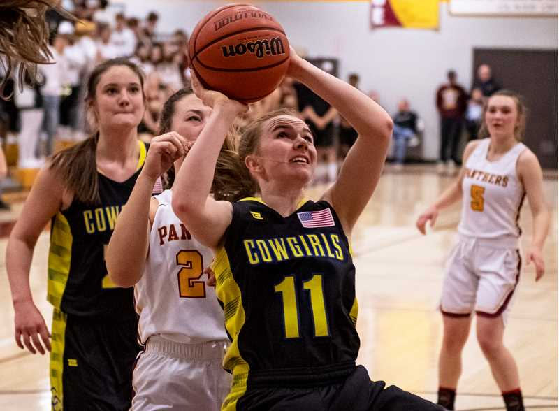 LON AUSTIN/CENTRAL OREGONIAN - Dallas Hutchins goes to the hoop for two of her 20 points as the Crook County Cowgirls came from behind to defeat the Redmond Panthers 58-42 Tuesday night in Redmond. The win gave the Cowgirls fourth place in the final Intermountain Conference standings.