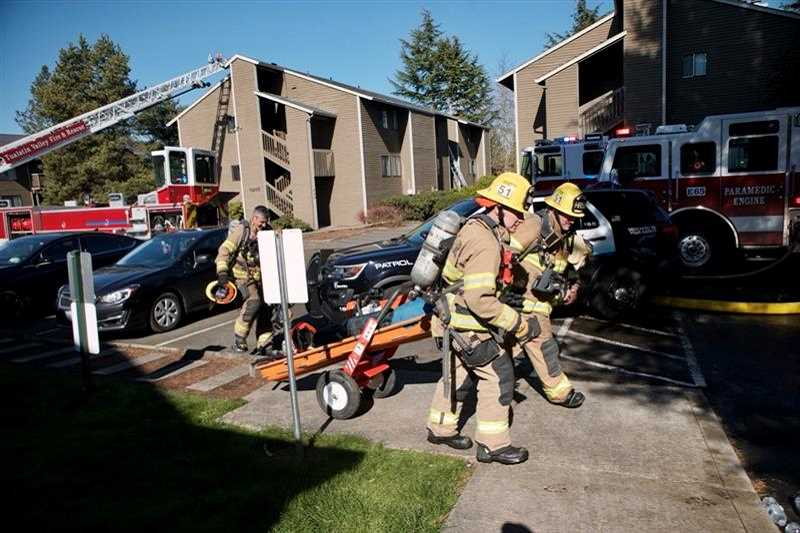 PMG PHOTO: JAIME VALDEZ - TVF&R firefighters clean up following a two-alarm fire that damaged two apartment units on Lombard Avenue Thursday morning.